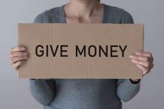 妇女拿着与题字的一副横幅给金钱 免版税库存图片