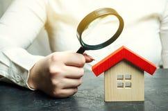 妇女拿着在一个木房子的一个放大镜 不动产评价人 对房子的情况的评估 免版税库存图片
