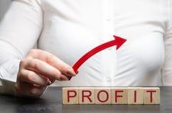 妇女拿着在木块上的一个箭头与词赢利 成功的事务的概念 收支成长和 库存照片