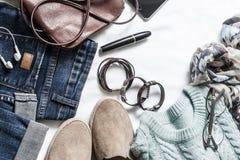 妇女的春天衣物集合-牛仔裤、绒面革运动鞋、套头衫,围巾和皮包 春天步行的妇女的衣裳在ligh 库存照片