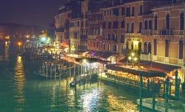 威尼斯,意大利- 02 23 2019年:在大运河停泊的长平底船在威尼斯 游人在户外舒适餐馆 大运河在晚上, 免版税库存图片