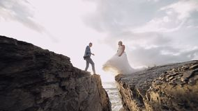婚姻的夫妇一起在山的倾斜在海附近的 可爱的新郎和新娘 慢的行动 股票视频
