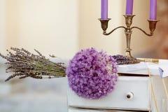 婚礼花束、蓝色蜡烛与烛台和玻璃用香槟 说谎在背景的桌上的淡紫色花束 免版税库存照片