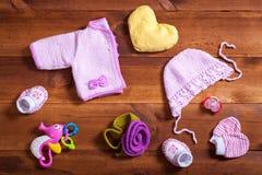 婴孩衣裳设置了概念、桃红色被编织的衣物、玩具和辅助部件在棕色木背景,儿童新出生的时尚布料为 库存照片
