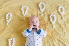 婴儿孩子顶视图围拢与惊叹号由咬住闹钟的棉花球做成在早晨 免版税库存图片