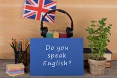 """学会语言概念-与文本""""的蓝纸;您是否讲英语?"""";英国的旗子,耳机,书 免版税库存图片"""