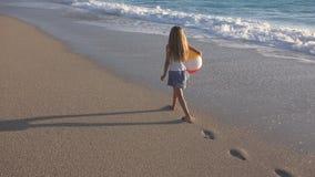 孩子使用在海滩的在日落,走在海海边的波浪女孩的愉快的孩子 免版税库存图片