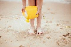 孩子在海滩使用 对沙子的水奔跑从喷壶 库存图片