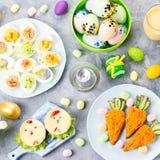 孩子的滑稽的五颜六色的复活节食物与在桌上的装饰 复活节晚餐概念 图库摄影