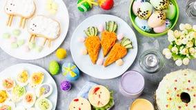 孩子的滑稽的五颜六色的复活节食物与在桌上的装饰 复活节晚餐概念 免版税库存图片
