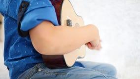 孩子的手的特写镜头 弹玩具吉他的小男孩 音乐,教育,生活方式,比赛发展和 影视素材