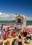 孩子观看多西特海滩的一个木偶戏表演 库存图片