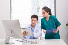 审查患者的医疗报告小组医生和护士 在患者的医生队在医院归档 免版税图库摄影