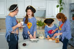 家庭一起烹调 丈夫、妻子和他们的孩子在厨房里 家庭揉面团用面粉 库存照片