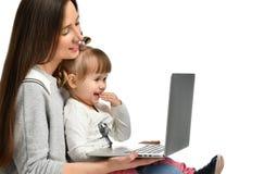 家庭母亲和儿童女儿在家有膝上型计算机的 免版税库存照片