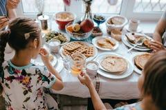 家庭早餐在家在好的舒适厨房里 吃薄煎饼的母亲、父亲和他们的两个女儿 免版税库存照片