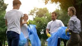 完成义务星期六工作的热心者家庭,采摘垃圾在公园 库存照片