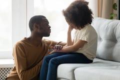 安慰哭泣的孩子女儿陈列同情的爱恋的非洲爸爸 免版税库存图片