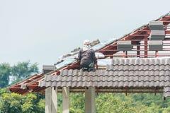 安装瓦的建筑盖屋顶的人在建筑工地 库存照片