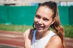 对照相机微笑美丽的运动年轻白肤金发的妇女的画象  免版税库存照片