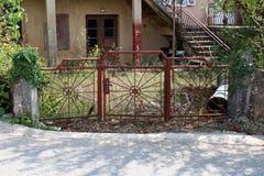 对被放弃的家庭房子的被铺的路入口阻拦与金属门锁与导致长得太大的前院的强的链子 图库摄影