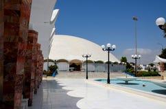对Masjid Tooba或圆的清真寺的喷泉走道与大理石圆顶尖塔和庭院防御卡拉奇巴基斯坦 免版税库存图片