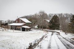 导致一个被风化的谷仓的积雪的车道 免版税库存照片