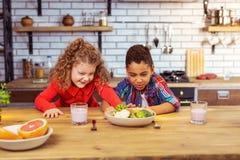 小孩做面孔,当看菜时 免版税库存图片