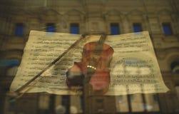 小提琴和弓在商店窗口里,音乐概念 免版税库存照片