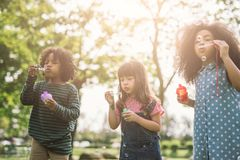 小组不同的孩子逗人喜爱的朋友获得在绿色草坪的泡影乐趣在公园 免版税库存图片