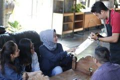 小组年轻愉快的朋友预定从菜单,当侍者在咖啡馆和餐馆时写命令 免版税库存图片