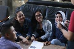小组年轻愉快的朋友预定从菜单,当侍者在咖啡馆和餐馆时写命令 免版税库存照片