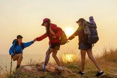 小组徒步旅行者帮助她的朋友的队妇女爬上日落的最后部分在山的 库存图片