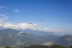 小组在多彩多姿的降伞的滑翔伞飞越一清楚的天空蔚蓝的山谷与白色云彩 免版税库存照片
