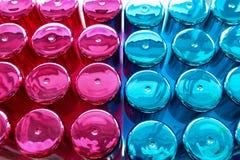 小组香水瓶五颜六色的蓝色和桃红色顶视图 背景瓶盖例证白色 免版税库存图片