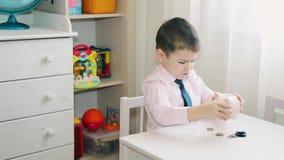 小男孩在存钱罐中计数积累金钱 影视素材