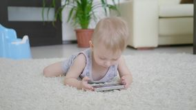 小男孩在家观看在智能手机的动画片在地板上,生活方式 股票录像