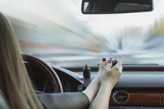 少女不安全地驾驶 油漆趾甲,当驾驶时 事故的概念,在轮子的不注意,危险 免版税库存照片