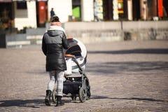 少女在欧洲城市的历史中心走与孩子s卡利 提高儿童户外在一个晴朗,晴天 库存照片