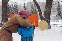 射击与箭头的一把弓的人教的男孩在俄国全国节日 库存照片