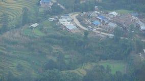 山麓小丘的小镇从上面 从在喜马拉雅谷,尼泊尔绿色土地安置的小和恶劣的镇空气的看法  股票录像
