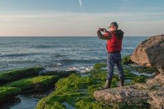 岩石海滨的旅客长满与拍照片的绿藻类 免版税图库摄影