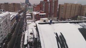 工业登山人在莫斯科清除从积累雪的一个屋顶 通风 影视素材