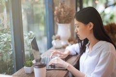 工作在有膝上型计算机的一咖啡馆的愉快的年轻亚裔女孩 免版税库存图片