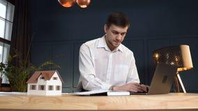 工作在新desing的年轻男性建筑师房子使用3d房子模型 股票录像