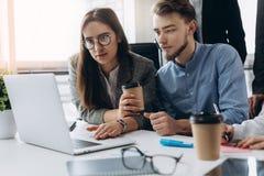 工作在现代办公室的年轻设计师夫妇  谈论在膝上型计算机的项目和喝咖啡的两个工友 库存图片