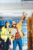 工作者在计划下个项目的后勤学仓库里 免版税库存照片