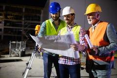 工程师、工头和工作者谈论在楼房建筑站点 免版税库存照片