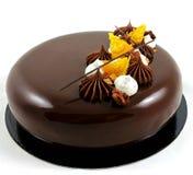 巧克力和橙色蛋糕与镜子釉和打好的奶油 免版税库存图片
