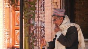 巴克塔普尔,尼泊尔- 10月13日抽烟在古城街道上的2018年长人  围巾和玻璃的种族人 股票录像